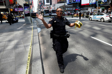 A New York City Police (NYPD) officer motions people to get back in Times Square after a speeding vehicle struck pedestrians on the sidewalk in New York City