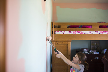 Side view of girl painting wall at home