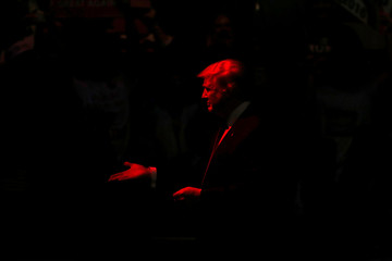 Trump is bathed in red stage light as he arrives to rally with supporters at an arena in Manchester, New Hampshire