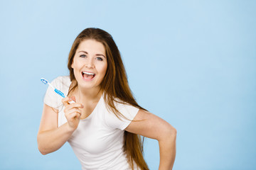 Happy woman holding toothbrush