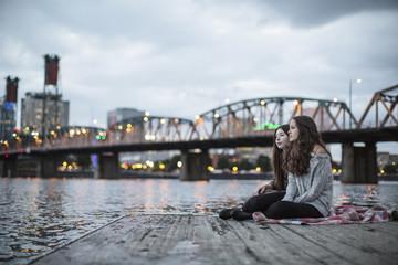 Female friends relaxing on pier against Burlington Rail Bridge