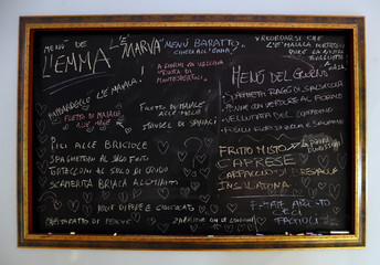 """A blackboard writing the """"Menu Baratto"""" (Menu Barter) is seen on the wall at the """"L'e'Maiala"""" restaurant in Florence"""