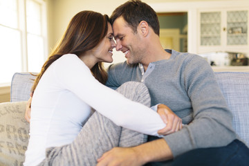 Smiling couple sitting on sofa at home