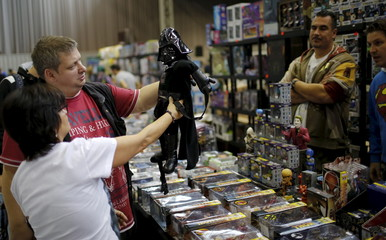 "Visitors look at a figurine from the movie ""Star Wars"" at the comic fair ""Vienna Comix"" in Vienna"