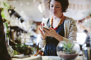 Cropped image of owner with customer using mobile phone for payment in plant shop