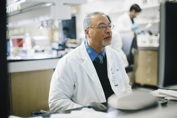 Doctor working at desk while male coworker working in background at hospital
