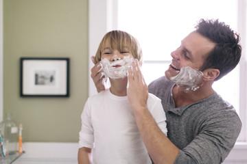 Father applying shaving cream to son in bathroom