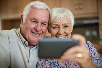 Senior woman taking selfie from mobile phone in kitchen