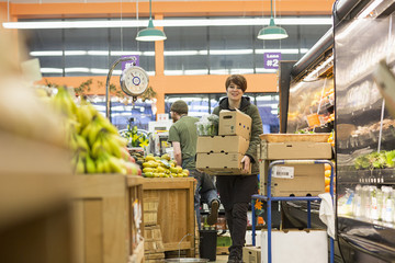 Female worker carrying boxes while working at supermarket