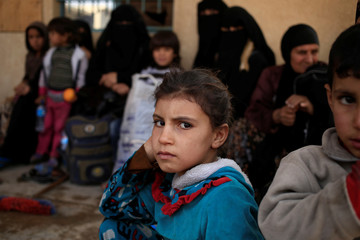 A girl who just fled the fighting between Islamic State and the Iraqi army sits with her family at a mosque used as a screening center near the frontline in Iraq