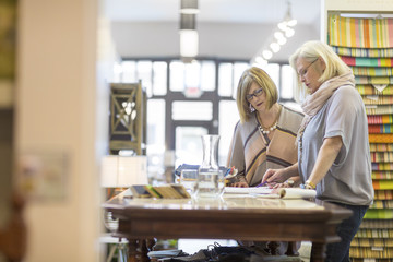 Female owners working at table in furniture store