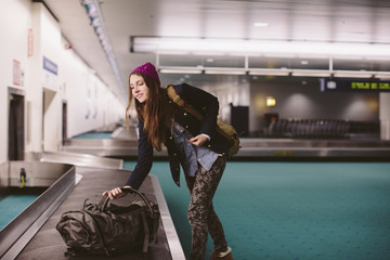 Woman carrying luggage from baggage claim at airport