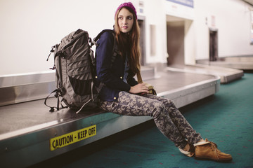 Woman with luggage sitting on baggage claim at airport