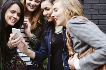Happy female friends looking at mobile phone