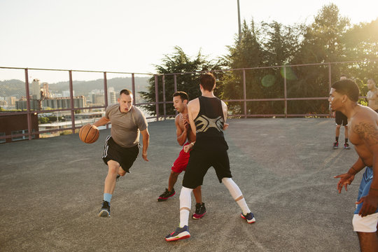 Male friends playing basketball in court against clear sky