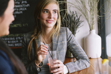 Woman looking at smiling friend while sitting in restaurant