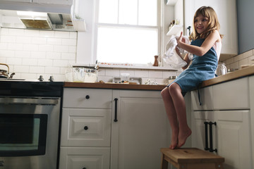 Smiling girl rubbing hands with napkin while sitting on kitchen counter at home
