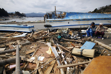 Fishermen take a break from cleaning the port devastated by the tsunami two weeks ago at the island of Oshima