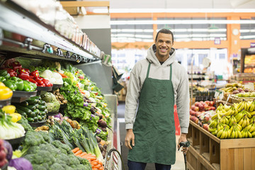 Portrait of smiling worker standing by shelves at supermarket