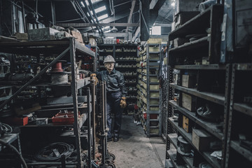 Female worker looking away while leaning on rack in factory