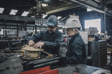 Coworkers making equipment at table in metal industry