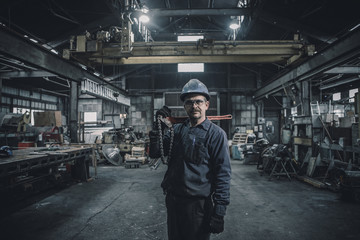 Portrait of male worker carrying work tool while standing in factory