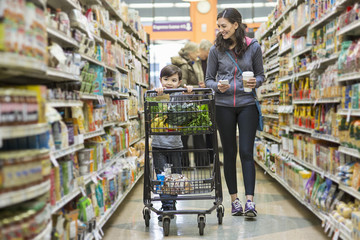 Woman walking by son pushing shopping cart at supermarket