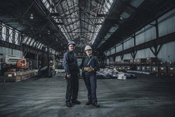 Portrait of confident coworkers standing in metal industry