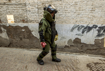 A technician from Pakistan's top bomb disposal unit walks during a bomb search operation in Peshawar
