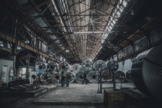 Side view of male worker walking by steel sheets in factory