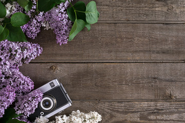 Lilac blossom on rustic wooden background with empty space for greeting message. Camera old. Top view