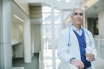Portrait of doctor holding disposable cup while standing in hospital