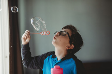 Boy wearing eyeglasses blowing bubbles at home