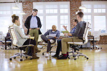 Business people planning while sitting on chairs in office