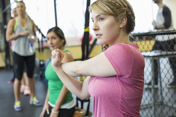 Woman stretching hands while standing with friends in background at gym