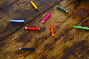 Colourful colour pencil over wooden table on summer background
