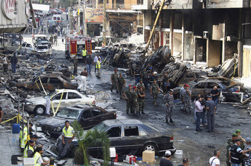 Lebanese army soldiers, military policemen, security forces and Hezbollah members inspect site of car bomb that occurred on Thursday in Beirut's southern suburbs