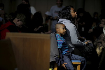 Seven-year-old Keith Merriweather and his mother Valencia wait for U.S. Democratic presidential candidate and U.S. Senator Bernie Sanders at a community forum about contaminated water in Flint, Michiga
