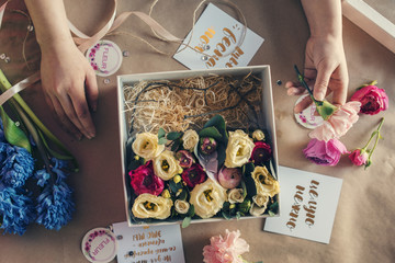 Overhead view of florist arranging flowers in box on table at flower shop