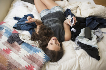 High angle view of playful woman using smart phone while lying on bed at home