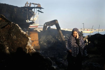 A Palestinian woman reacts as she looks at her son's boat, which police say was damaged in a fire following an Israeli naval strike, at the seaport of Gaza City
