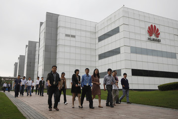 Employees of Huawei Technologies Co. Ltd. walk past the company office in Shenzhen, Guangdong province