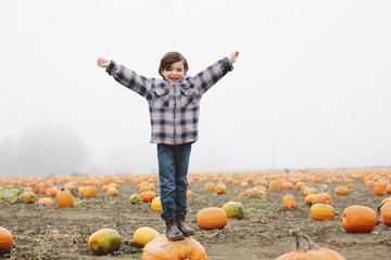 Portrait of happy boy with arms outstretched standing on pumpkin at farm during foggy weather
