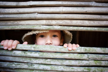 Portrait of boy looking through bamboo fence