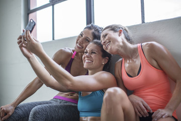 Happy female friends taking selfie through mobile phone in health club