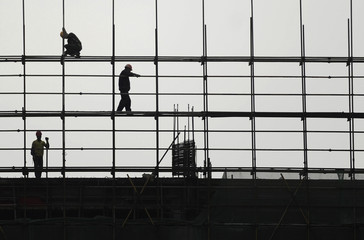 Labourers work on scaffolding at a residential construction site in Hefei