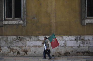 Man holds a Portuguese national flag as he shouts slogans against government policies in downtown Lisbon