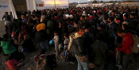 Migrants wait to enter a transit camp in Gevgelija