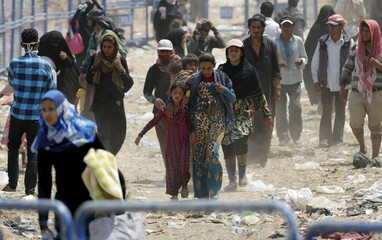 Syrian refugees walk to cross into Turkey at Akcakale border gate in Sanliurfa province
