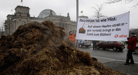Activists from anti-globalisation organisation Attac protest next to dung pile in front of Reichstag building in Berlin